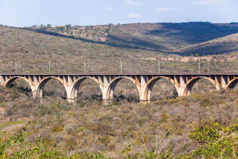 Train Railway Arched Bridge Valley Landscape. Train railway arched bridge vintage structure across dry winter valley landscape royalty free stock image