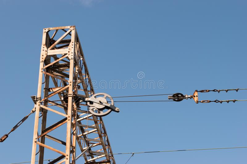 Train or railway power line support. Railway power lines with high voltage electricity on metal poles against blue sky. royalty free stock photo