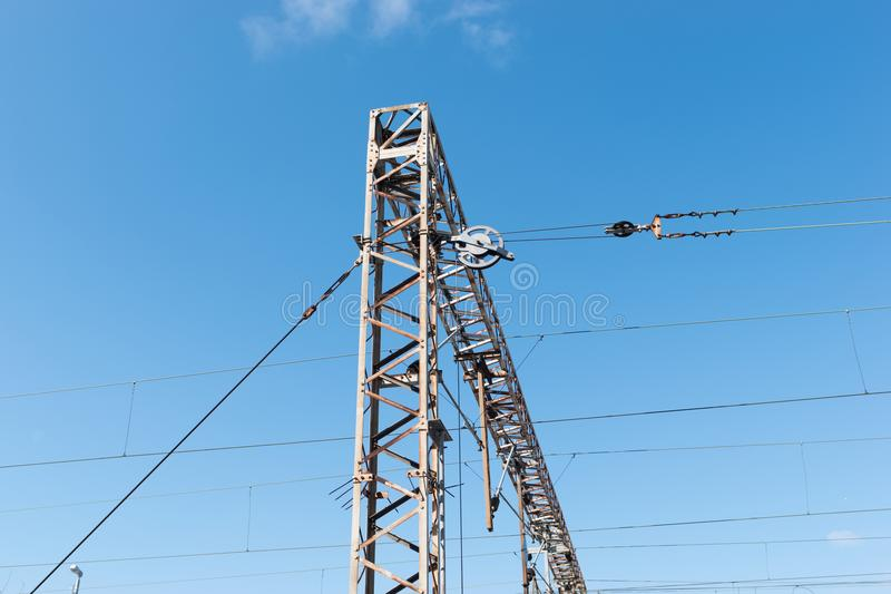 Train or railway power line support. Railway power lines with high voltage electricity on metal poles against blue sky. stock image