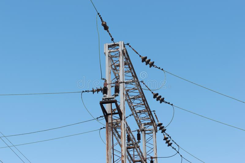 Train or railway power line support. Railway power lines with high voltage electricity on metal poles against blue sky. royalty free stock image