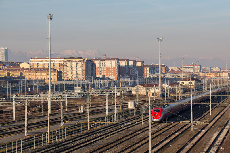 Train on railways with typical buildings and muontains on background. Lingotto district. Turin. Italy. stock photos