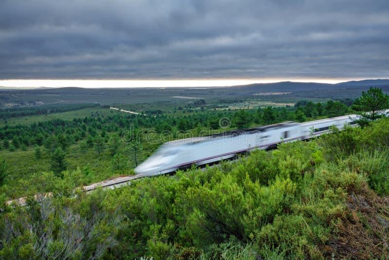 Train rapide ferroviaire et brouillé dans le pays au lever de soleil images libres de droits