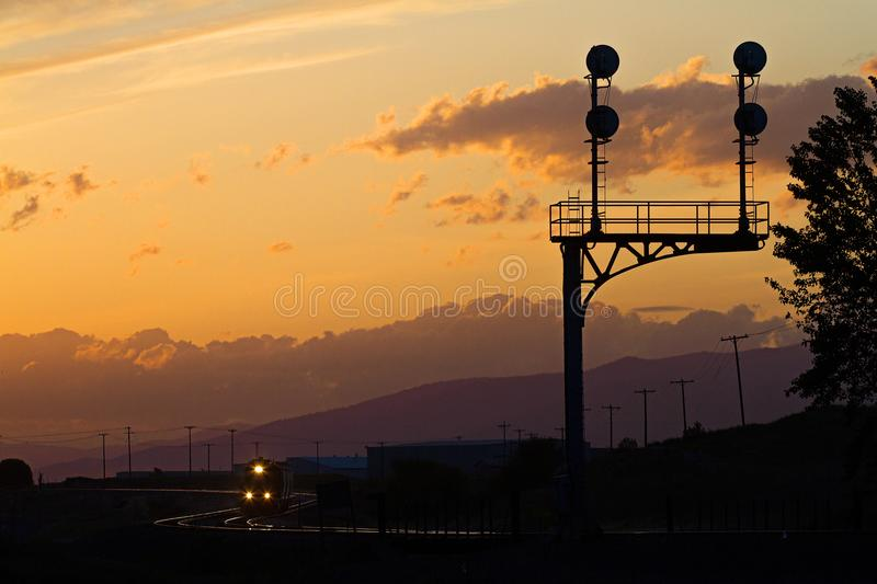 A train rolls through curves at sunset stock photo