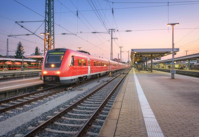 Train rouge à grande vitesse sur la gare ferroviaire au crépuscule image libre de droits