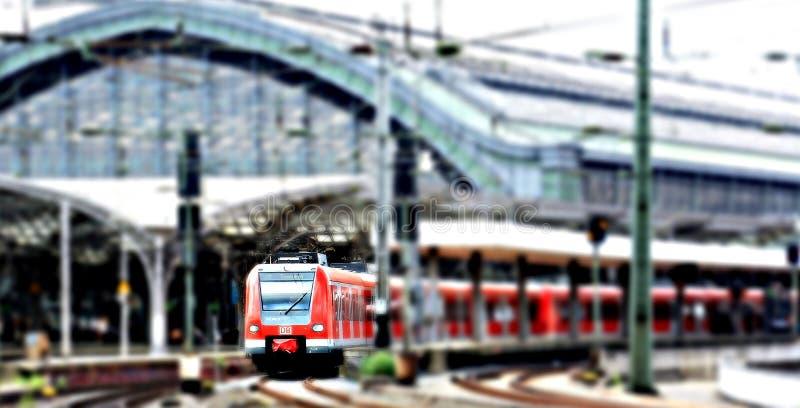 Train rouge à une station de train verte un jour obscurci photo libre de droits