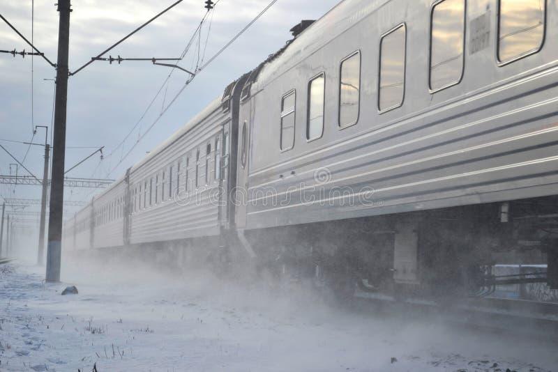 Train running through blizzard. Winter train running through snowstorm royalty free stock photos