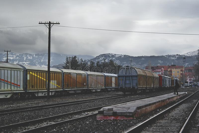 Train Running on Train Track Under Gray Sky at Daytime royalty free stock image