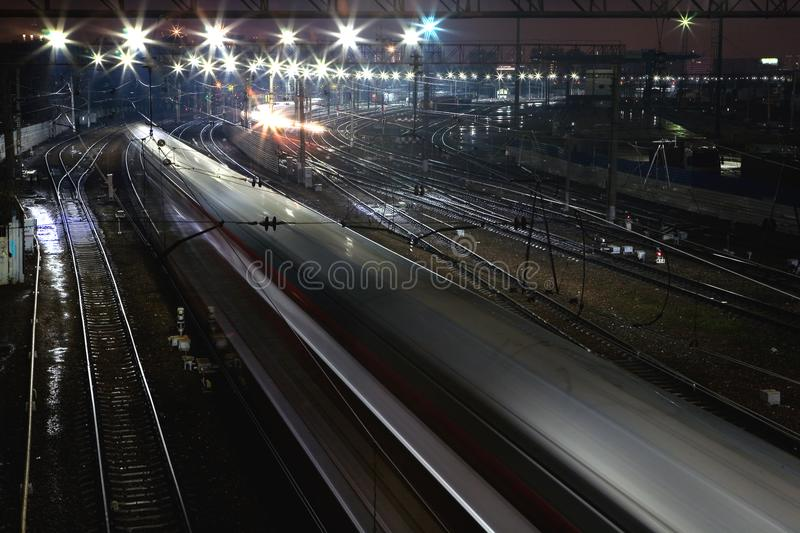 The train rushes on the rails at night. View from above stock images