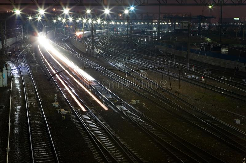 The train rushes on the rails at night. View from above royalty free stock photo
