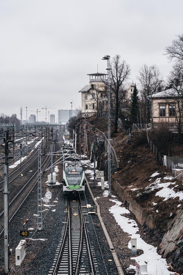 Train se déplaçant sur les rails vers Helsinki une journée de printemps brumeuse avec de la gauche de neige photos stock