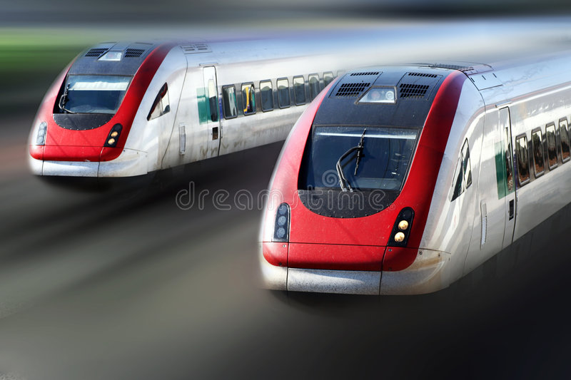 Train Series. Two trains travelling very fast along its tracks stock photo