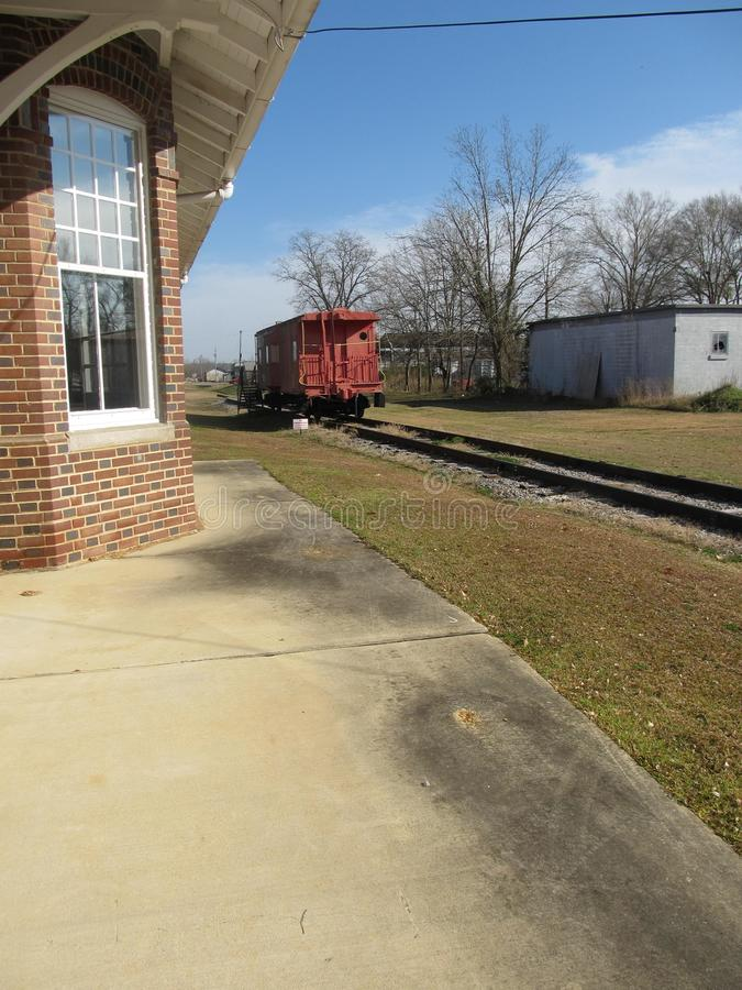 Train station with caboose in distance. An old railway station with brick building, platform and caboose in distance, which accommodates railway workers, blue stock photography