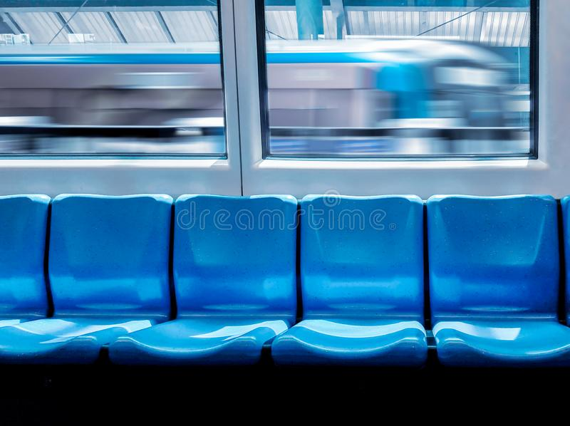 Train station and empty seats commuter with blue color interior inside in the subway train royalty free stock photos