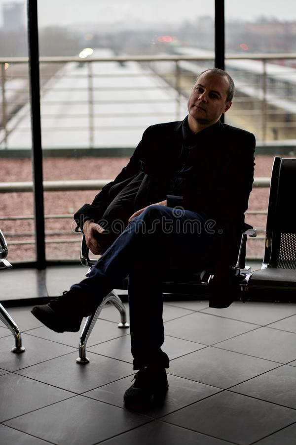 Train Station. A mature man in business clothes and a coat is sitting in a waiting room stock photography
