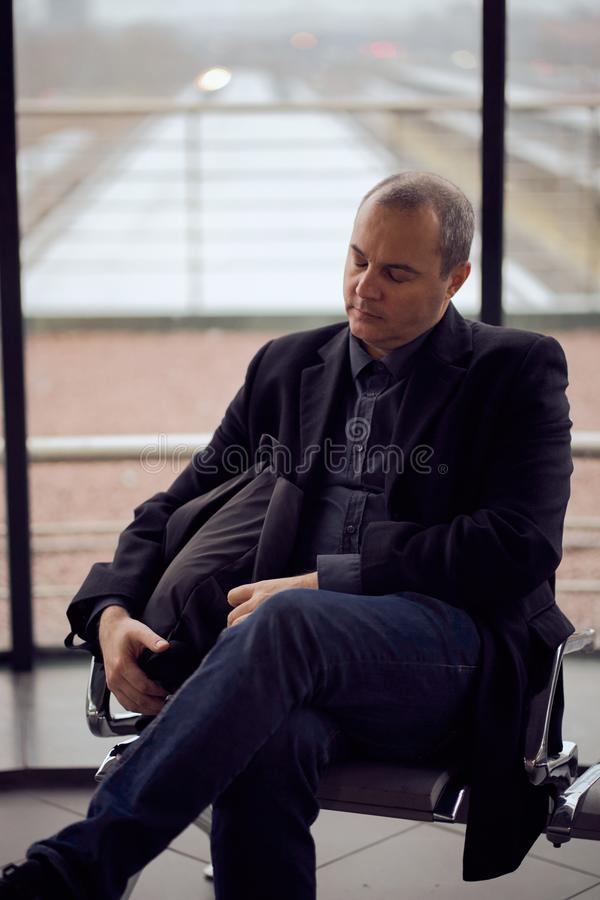 Train Station. Mature man in business clothes is sleeping, sitting in waiting room and waiting for train. Evening is dark. Vertical royalty free stock image