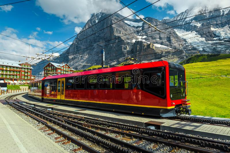 Train station with mountains and modern tourist train, Grindelwald, Switzerland stock image