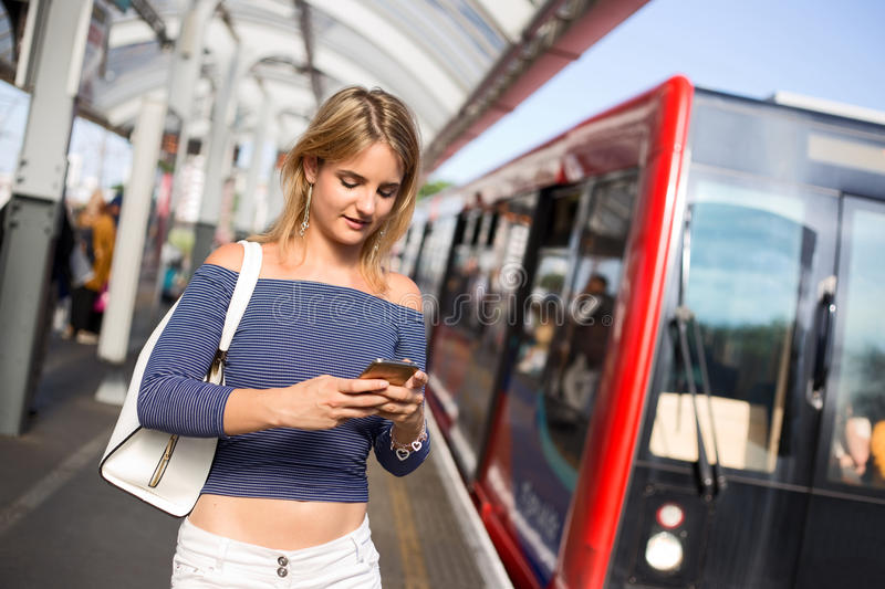 Train station. Young woman at the train station using her phone stock images
