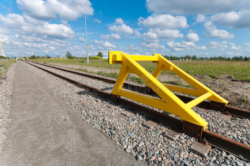 Train stop. Yellow buffer stop at the end of a railroad track royalty free stock photography