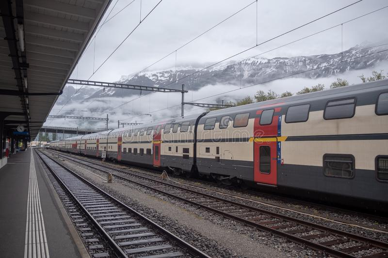 Train stops in empty station on foggy mountain background. With copy space stock image