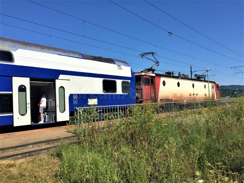 Train to Breaza stop, Prahova Romania. Blue train stopped at Breaza station which is littered with weeds on a sunny day. Breaza, Prahova, Romania royalty free stock images