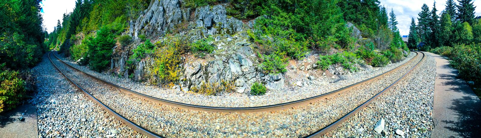 Train Track Curve. Whistler, BC, Cananda - Sept. 21, 2016: Distorted perspective panorama of railroad tracks skirting through Whistler, near Alpha Lake. Tracks royalty free stock photos