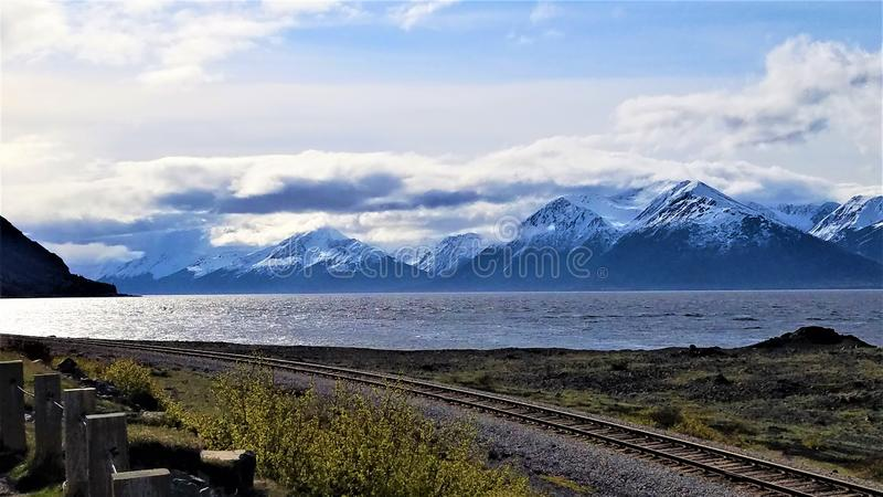 Train tracks adjacent to the Cook Inlet Alaska. Parting clouds allow sunlight to shimmer on the Cook Inlet near Turnagain Arm south of Anchorage as train tacks royalty free stock image