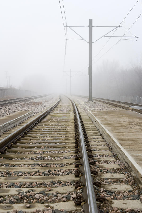 Train Tracks Disappear Into Fog. Some train tracks disappear into thick fog royalty free stock images