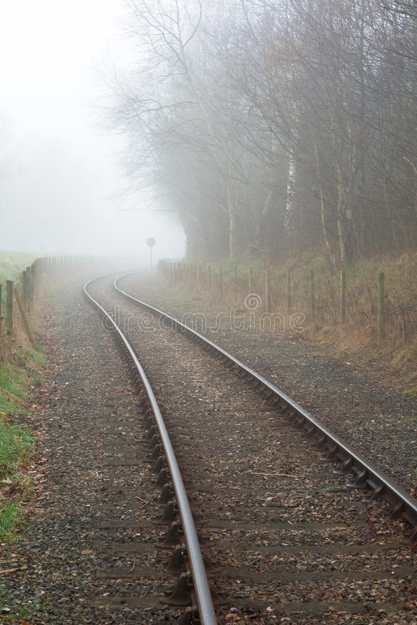 Train Tracks disappear into foggy distance. Train track disappearing round bend into the distance obscured by fog and mist. Portrait Format image stock photography