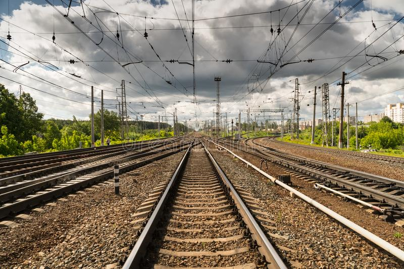 Train tracks go over the horizon line. Cloudy sky stock image