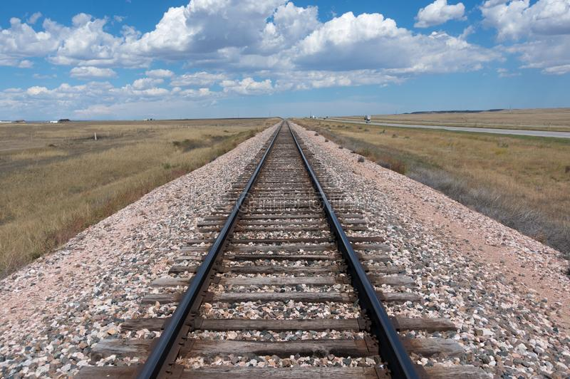 Train Tracks on an Open Plain Stretching Out to a Blue Sky and Clouds on the Horizon. And Grassy Field on Either Side stock photos