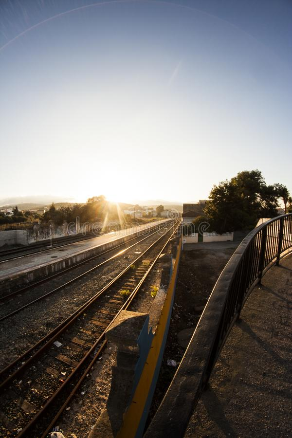 Train tracks in the sunset. A train tracks arriving at the station during sunset. chopped vision and no trains around. In the background are the mountains and royalty free stock images