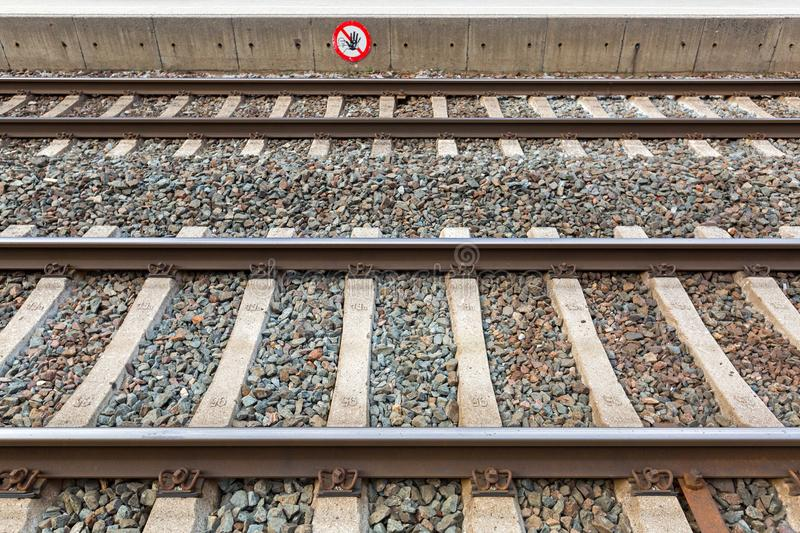 Train tracks at train station with crossing forbidden sign in Ra stock photo