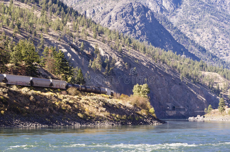 Train and train tunnel. A train approaches a mountain train tunnel by the Thompson river near Goldpan Provincial Park near Spences Bridge, BC, Canada stock images