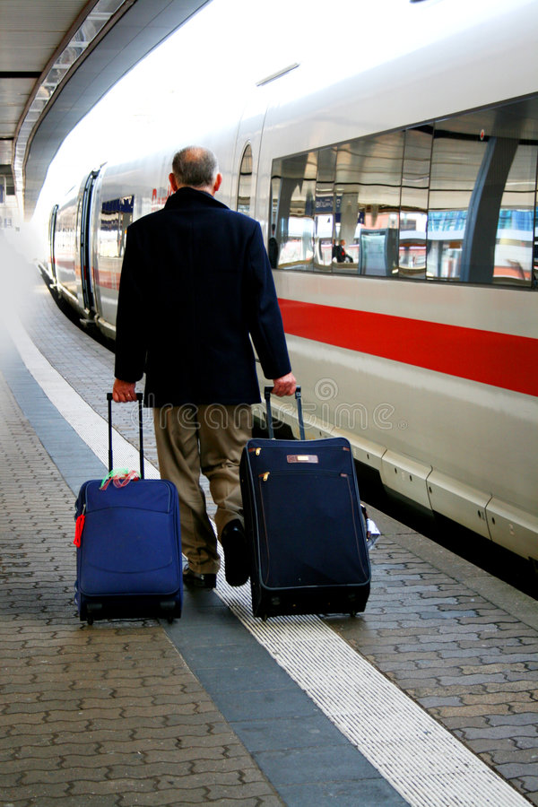 Train traveller. Senior traveller carrying 2 luggages in a hurry to board a waiting high-speed train