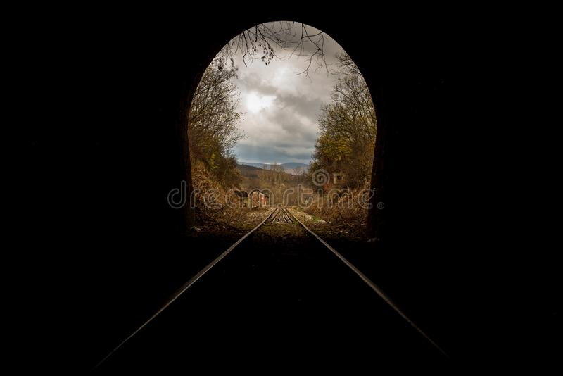 Train tunnel end in picturesque rural scenery royalty free stock image