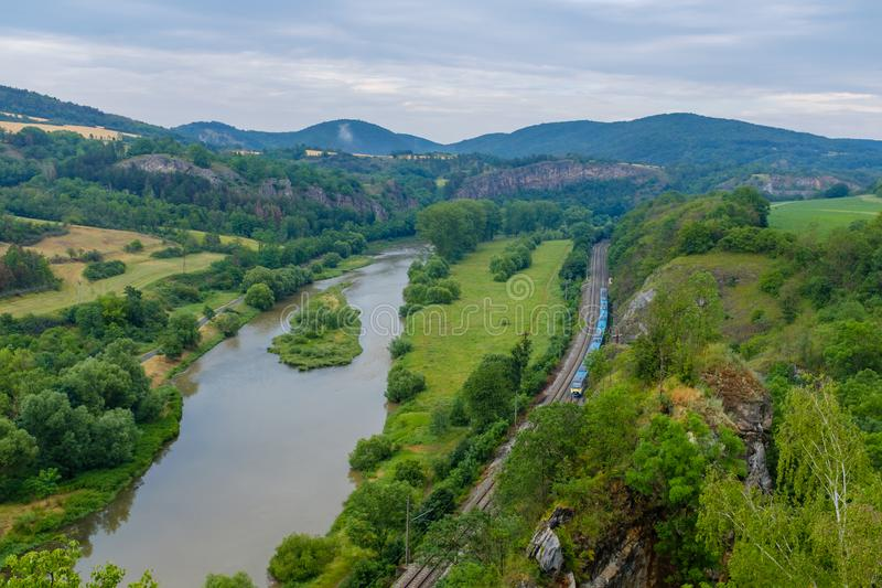 Train in a valley by a river stock photography
