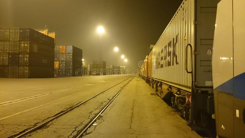 Train with wagons in port at night stock photo