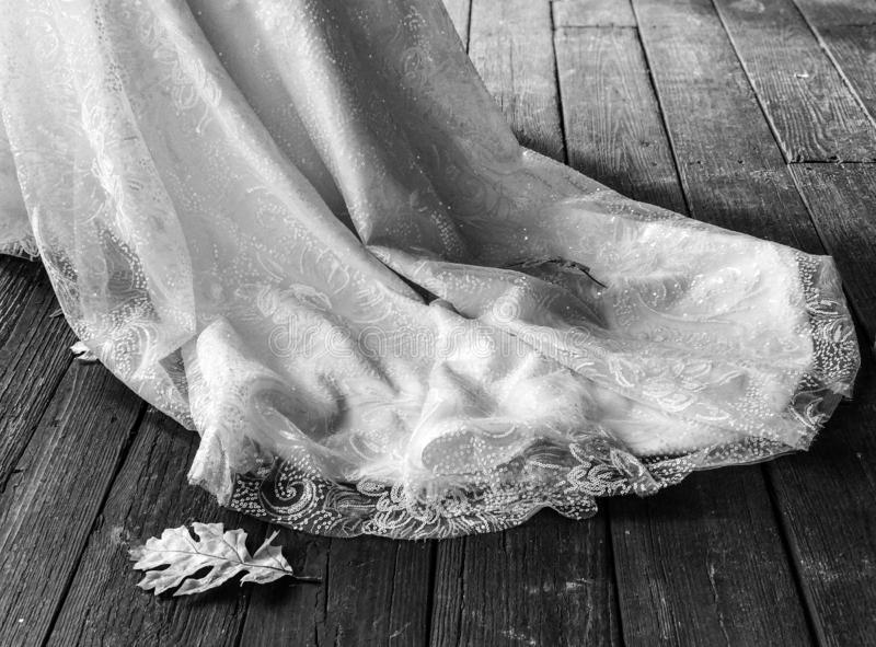 The train of a white wedding dress lays on the ground and is illuminated by natural sunlight - WEDDING DRESS. A train is an extra length of fabric that extends stock photos