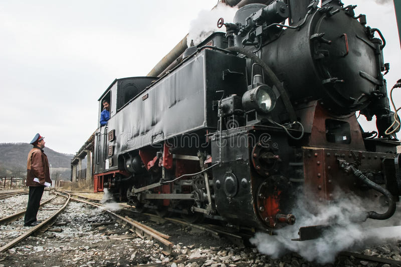 Train workshops with running bridge. Brad, Romania, December12, 2009: An old steamed cog train in Brad, on winter holydays royalty free stock image
