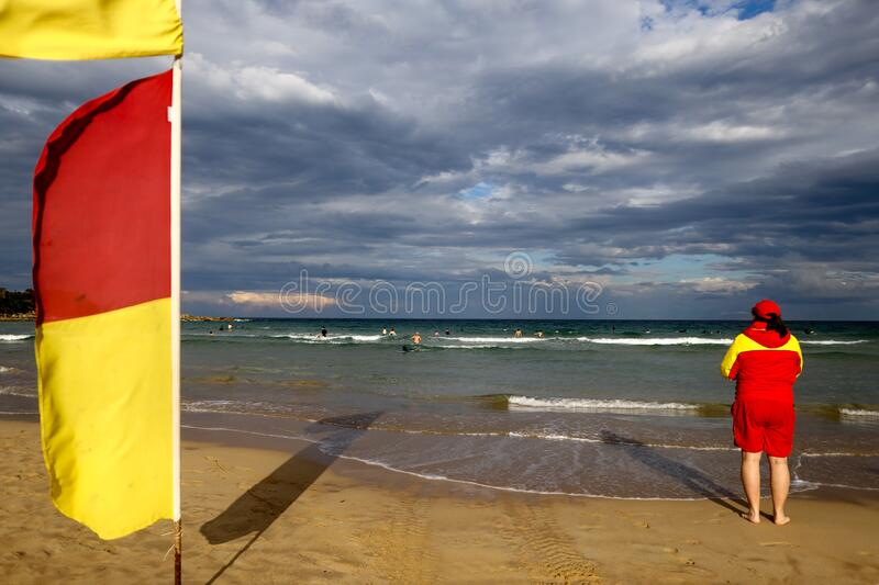 Trained competent female lifeguard beach patrol wearing red yellow shirt standing on the beach watching ensuring tourists swimming. Between flags defocused stock image