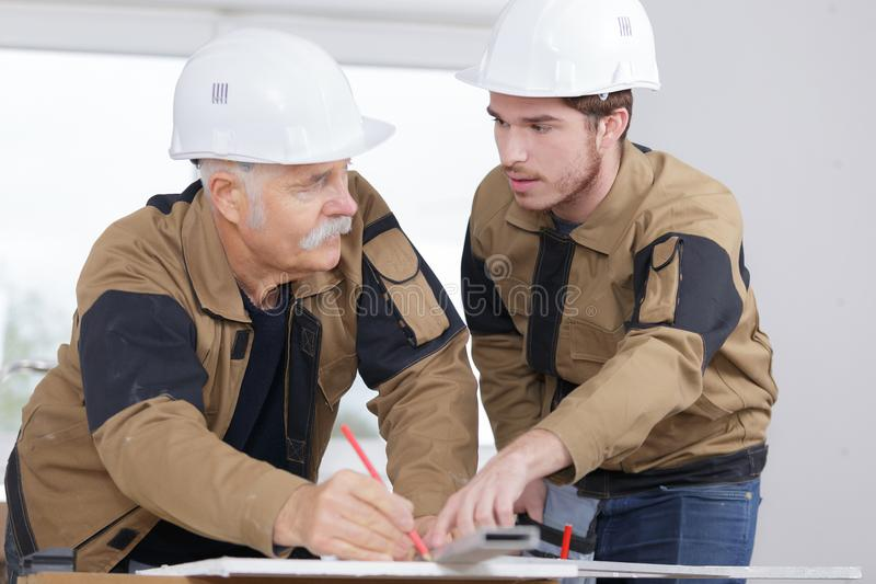 Trainee carpenter with mentor stock photography