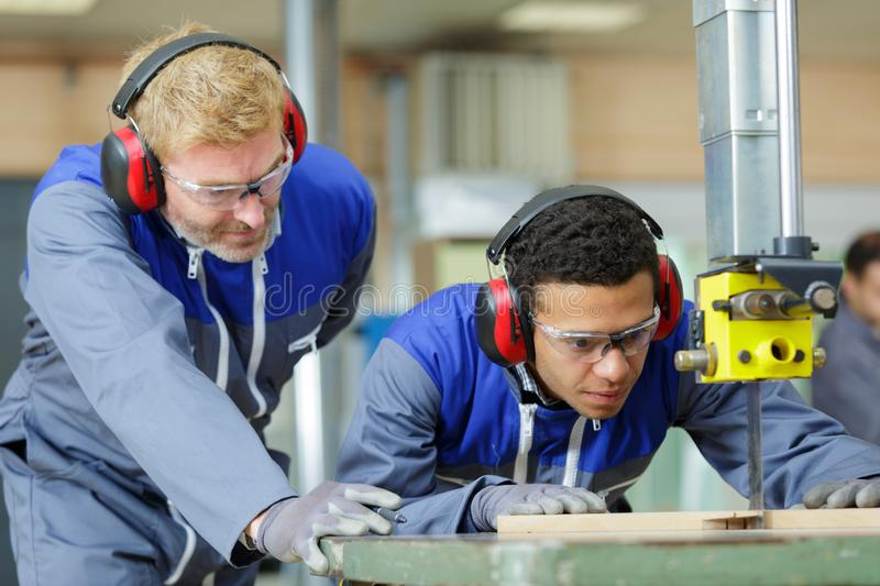 Trainee carpenter using band saw under supervision. Apprentice royalty free stock photos