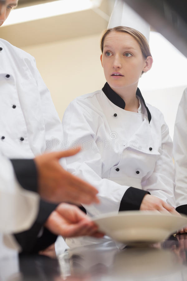 Trainee chef listening to teacher. In culinary school stock photo