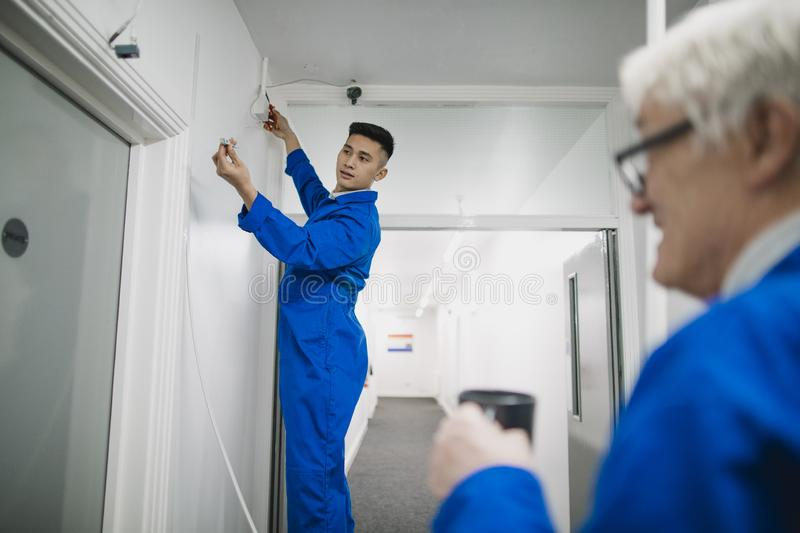 Trainee Electrician Fitting a Security Camera royalty free stock images