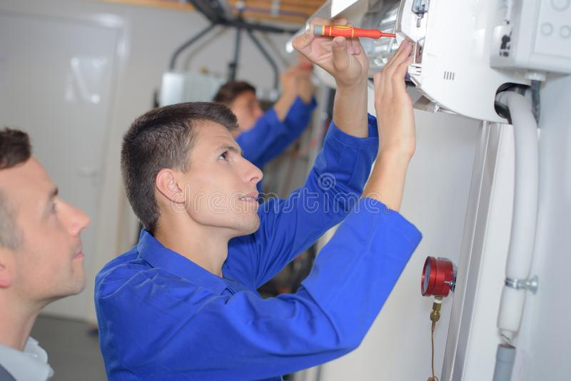 Trainee electrician working on fuse box stock images