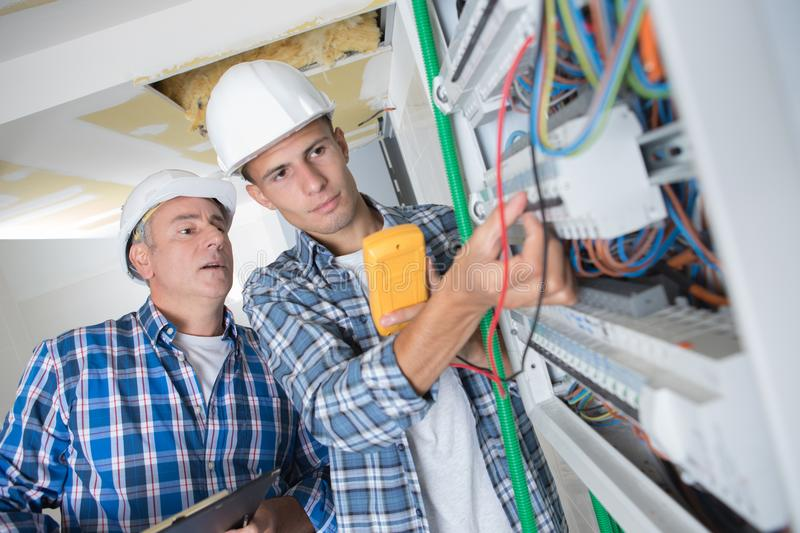 Trainee electrician working on fusebox under supervision. Apprentice royalty free stock photography