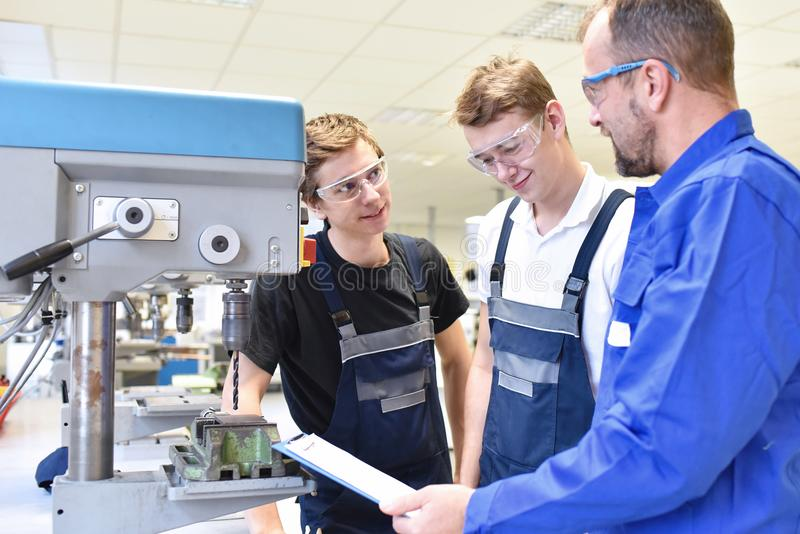 Trainer and apprentice in technical vocational training at a drilling machine stock photo