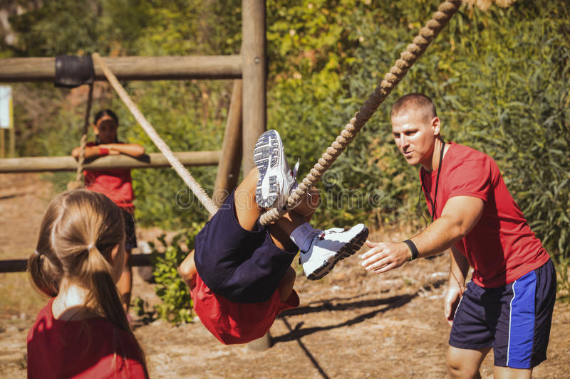 Trainer assisting a boy in obstacle course training royalty free stock images