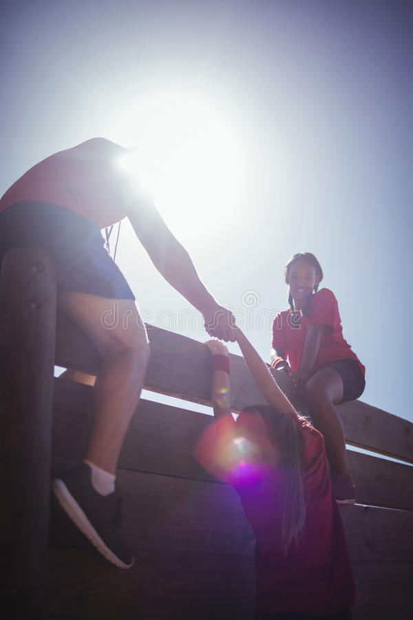 Trainer assisting kids to climb a wooden wall during obstacle course training stock image