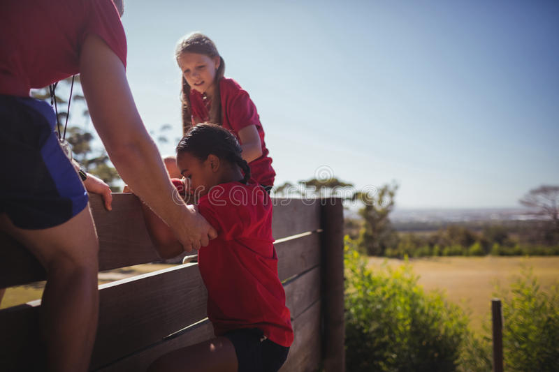 Trainer assisting kids to climb a wooden wall during obstacle course training stock images